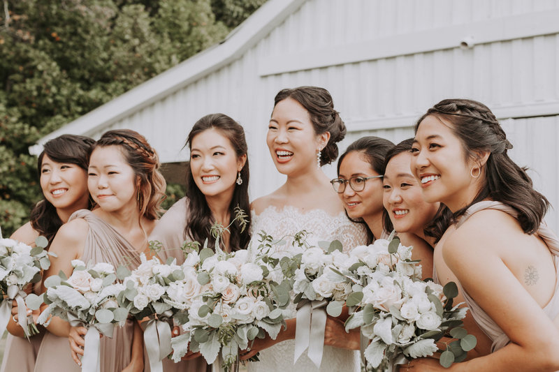 Bride and bridesmaids smiling with flower bouquets