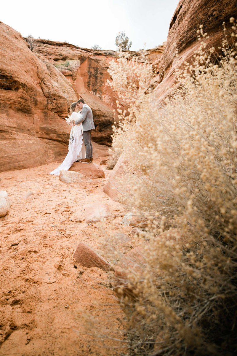 couple hugs at the opening of the slot canyon