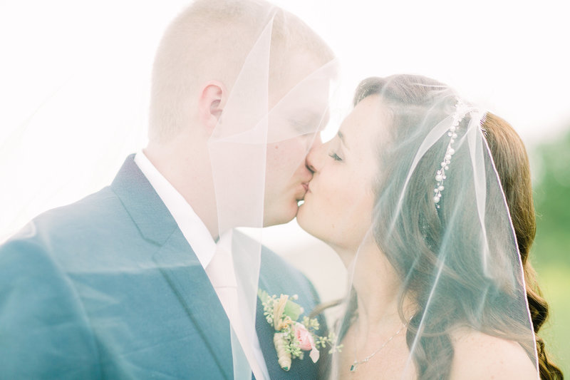 Bride and groom, Liz and Tyler, kiss under Liz's veil