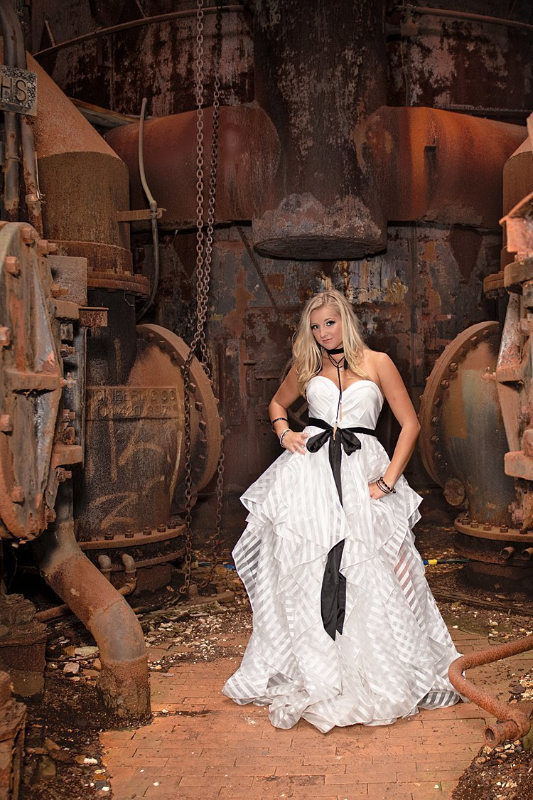 High school senior girl in tiered white dress with black sash standing among rusted steel at Carrie Furnace in Pittsburgh, PA