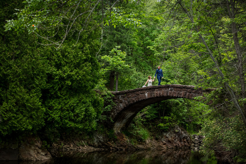 Couple crossing bridge with green trees
