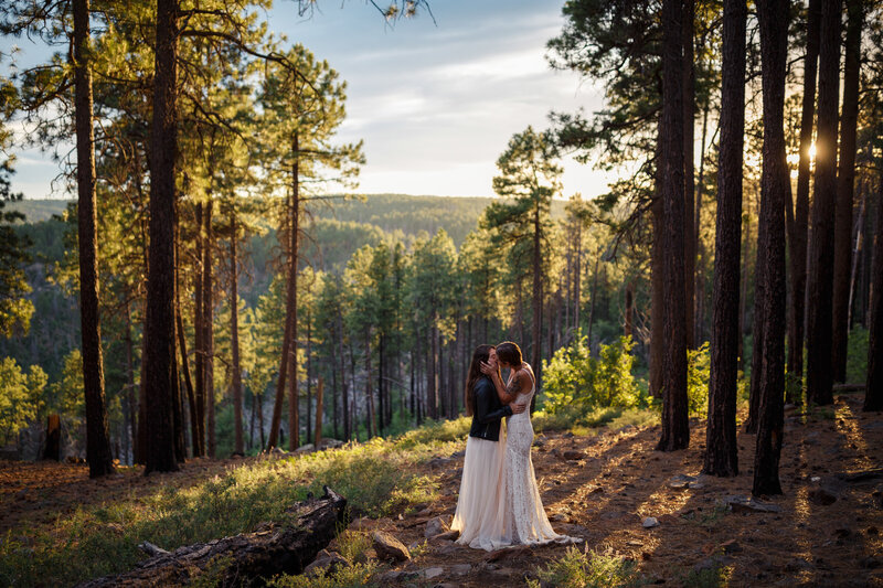 moody woodsy elopement in the forrest with two brides kissing