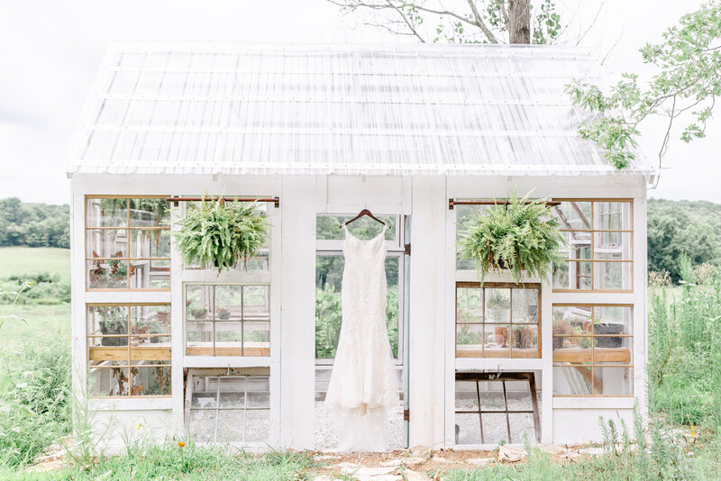 A fit and flare wedding gown hangs from the white, rustic greenhouse at Rose Oak Acres.