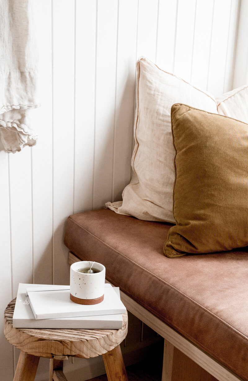 pillows on window seat with table and mug with tea