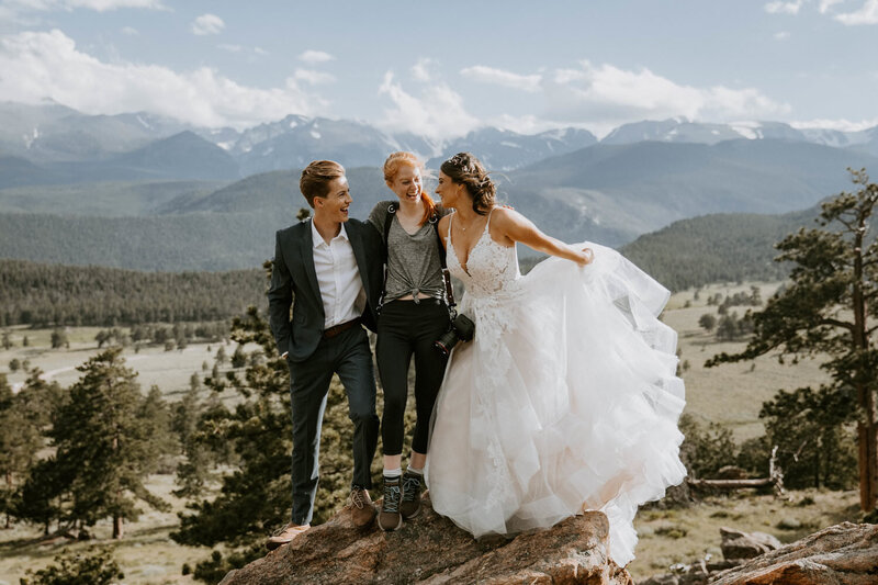 brides standing with photographer with mountains in background