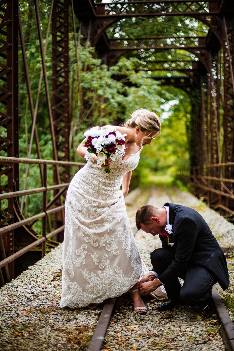 Groom fixes bride's show strap on train trestle at  Barn at Conneaut Creek