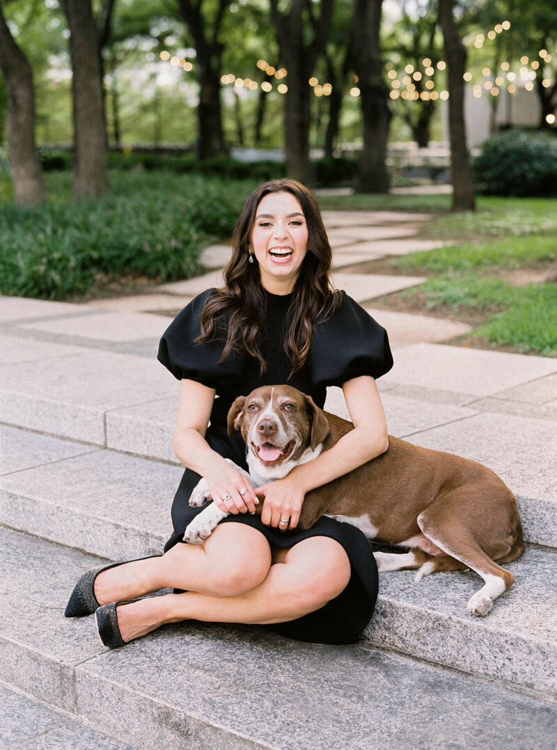 woman in black dress aughing sitting next to smiling pitbull dog