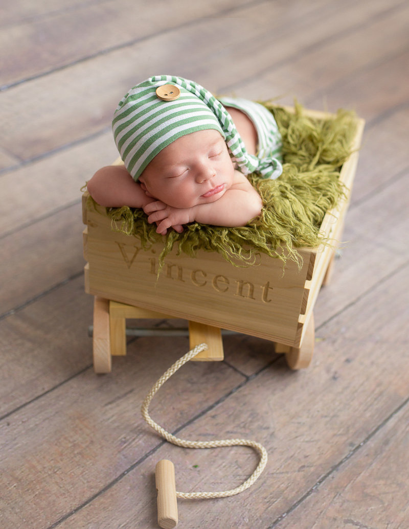Newborn boy posed in a wagon in our Rochester NY studio.