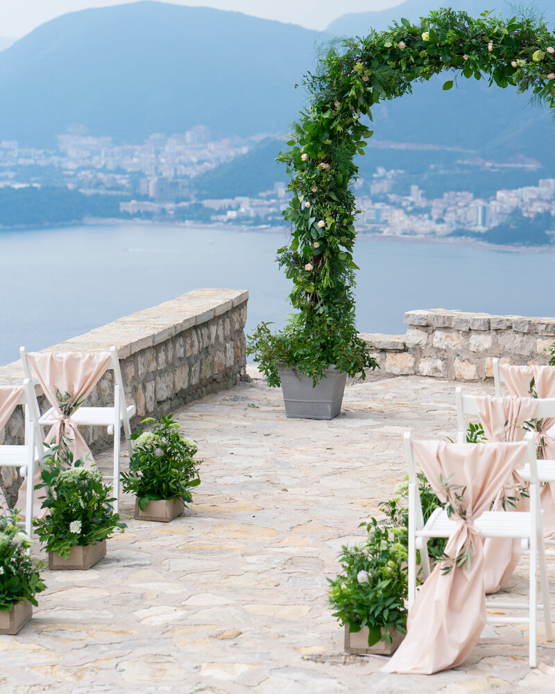 A decorated wedding arch of greenery frames the ceremony aisle at a destination wedding overlooking the ocean in