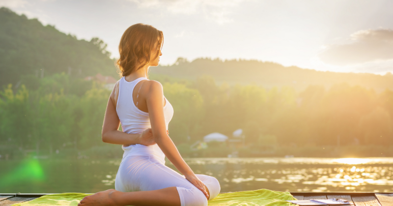 A woman holding a yoga pose on a dock looking out at the lake