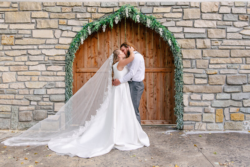 A bride and groom kiss in front of a stone archway.