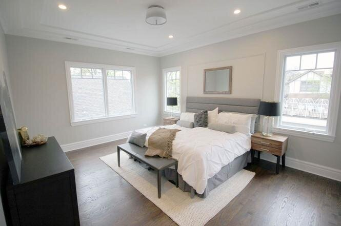 Magnolia master bedroom with light grey upholstered headboard white bedding light natural wood nightstands and a black wood dresser