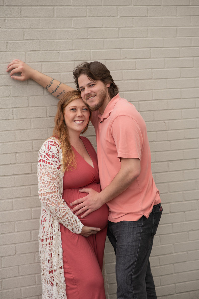 Husband & Pregnant wife snuggling and leaning on white brick wall