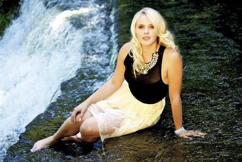 Female musician portrait Jrista Earle sitting at edge of waterfall