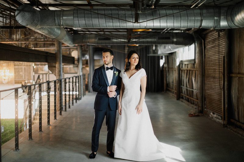 man in blue tuxedo and woman in white wedding dress standing side by side in dark industrial space