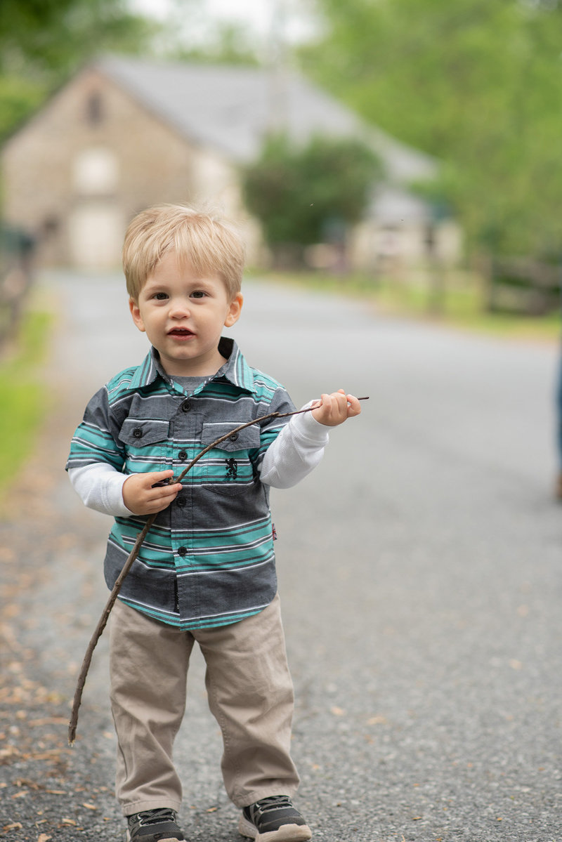 Little boy holding stick in front of barn