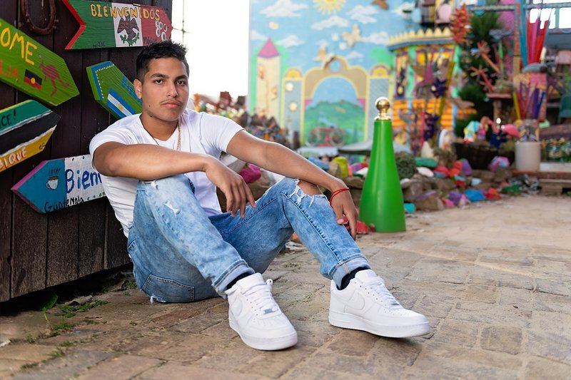 High school senior boy in white Polo tee and ripped jeans seated on ground in front of gate covered with colorful signs at Randyland in Pittsburgh, PA