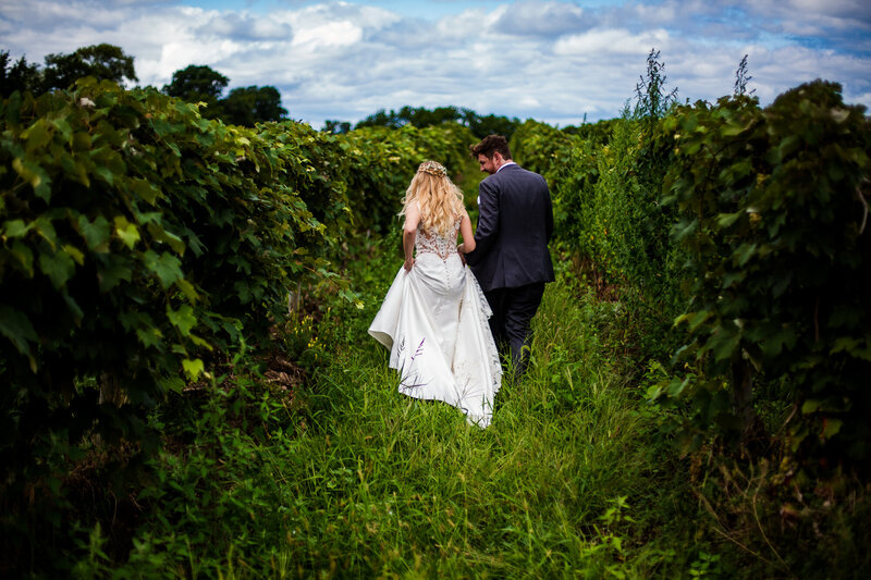 Couple walks through the vineyard at Quincy Cellars before their wedding