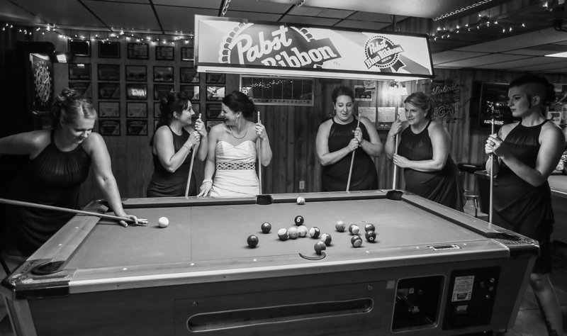 Bride and her bridesmaid gather around a pool table at an Erie, PA social club