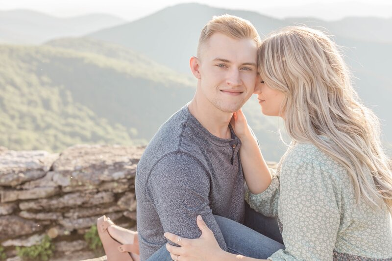couple straddle each other on mountain for engagement photos