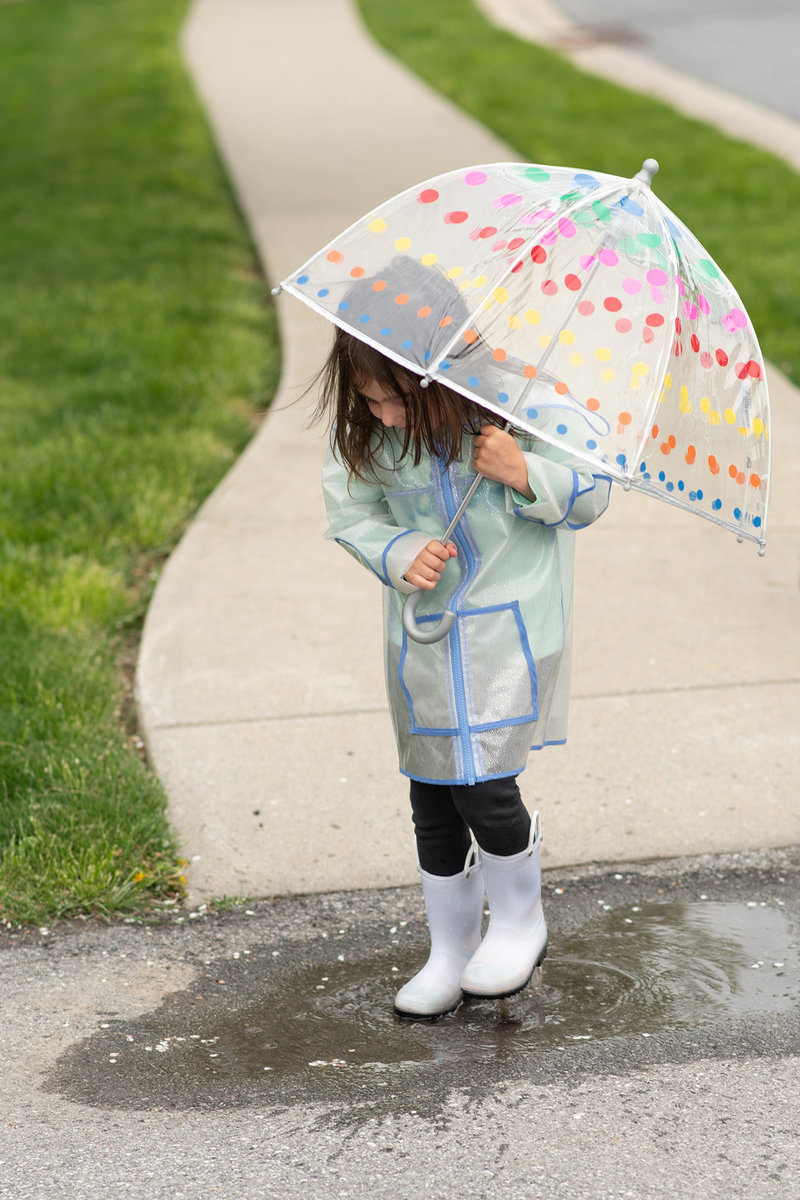 Little girl splashing in puddle with rain boots and umbrella