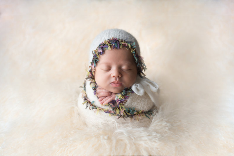 newborn baby girl swaddled in potato sack pose