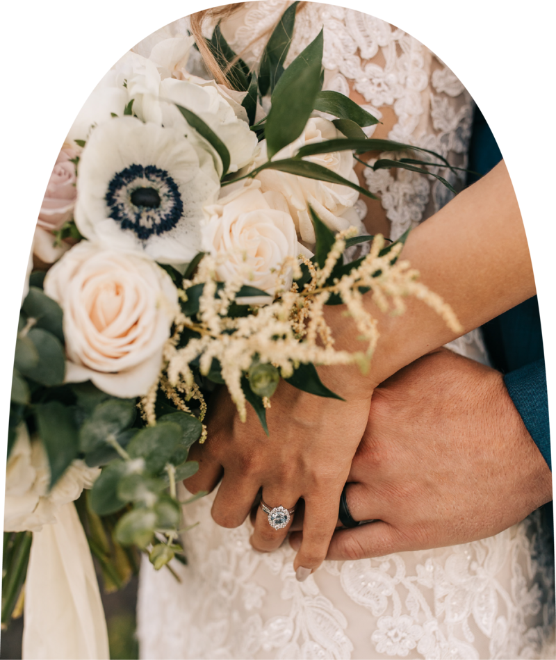 Bride and groom holding hands featuring bride's ring