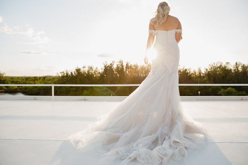 View of a bride in wedding gown from behind as the sun shines through