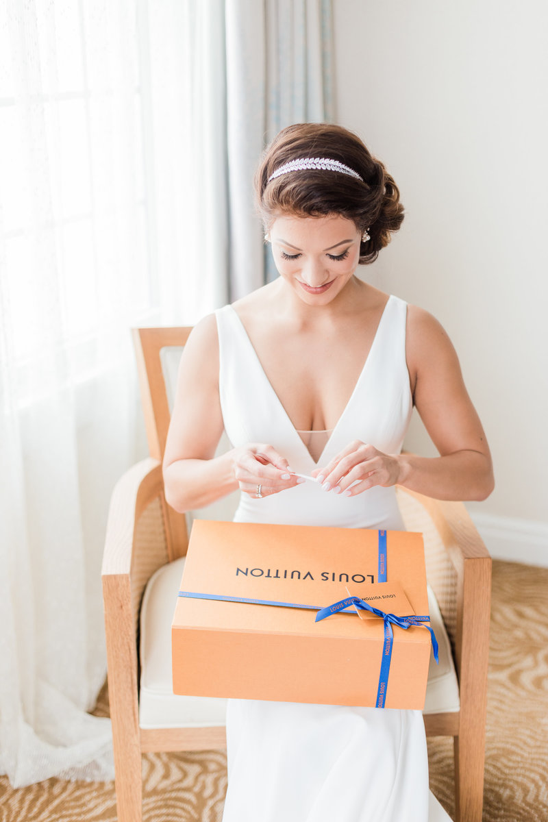 bride opening up louis vuitton gift from groom at Don Cesar Wedding Photographer in St. Petersburgh Florida by Costola Photography
