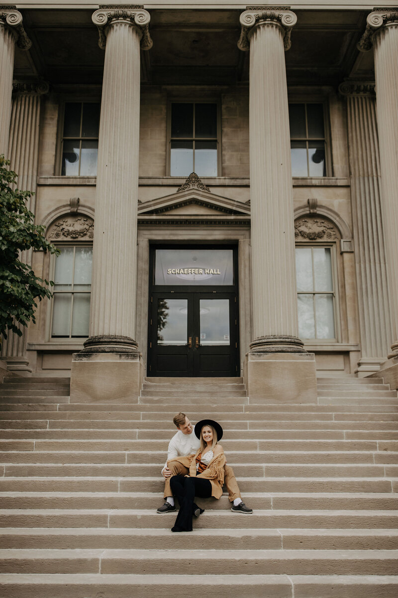 Engaged couple sit on a huge outdoor staircase as the girl smiles at the camera and her fiance snuggles into her neck. Photo taken by The Creative Des Moines Iowa Photographer