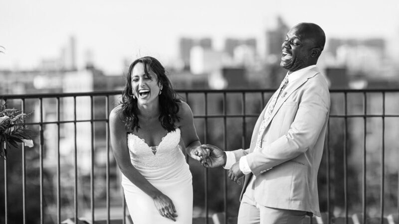 A bride and groom holding hands and laugh on the rooftop of lacuna lofts.
