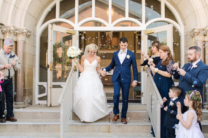 Bride and groom walk down the steps outside of the church after their wedding ceremony as guests blow bubbles