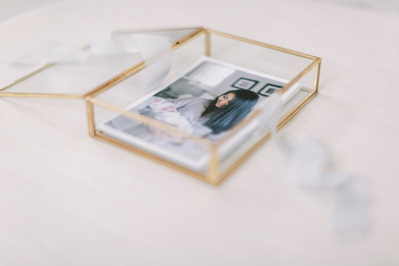 Luxury newborn photos in gold box wrapped in fine ribbon