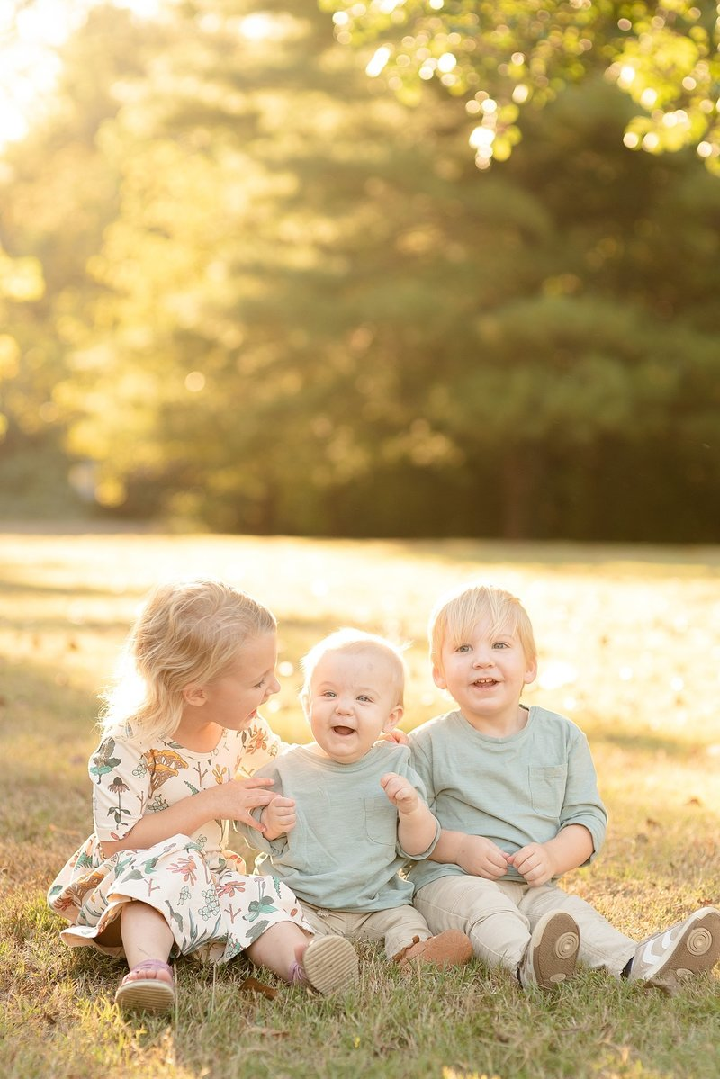 Three siblings are sitting on the grass in Green Hills Nashville Tennessee for family portraits with Dolly DeLong Photography