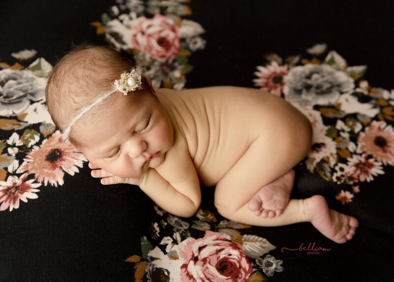 Calgary Newborn posed on a black floral blanket