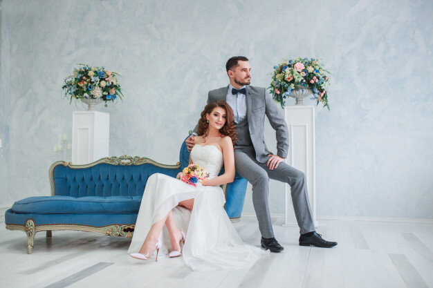 bride-beautiful-dress-groom-gray-suit-sitting-sofa-indoors-trendy-wedding-style_153585-127