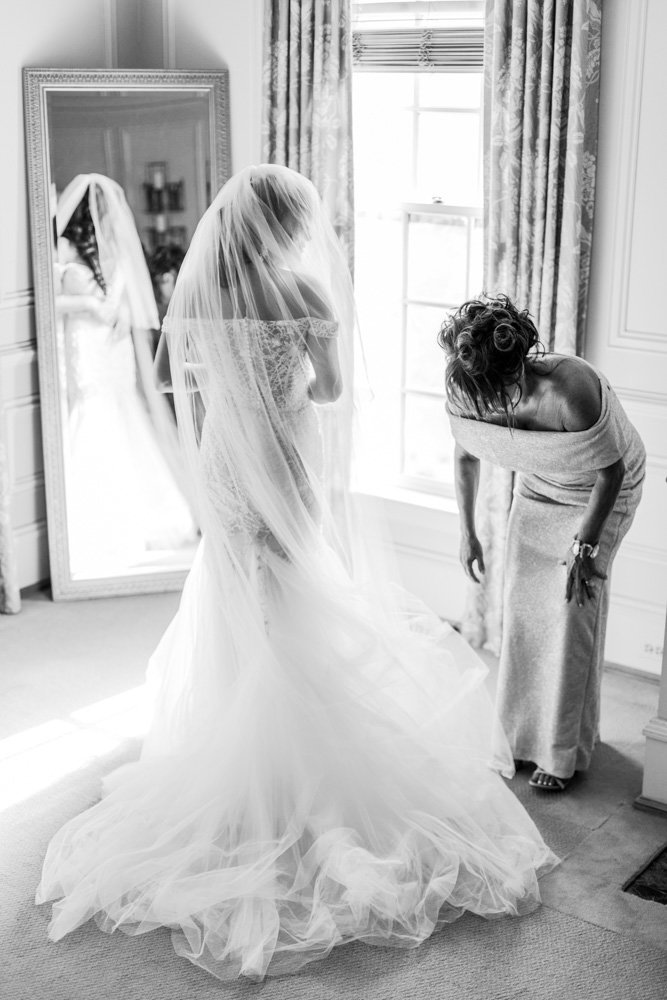 bride getting dressed in bridal suite at great marsh estate wedding in northern virginia by costola photography
