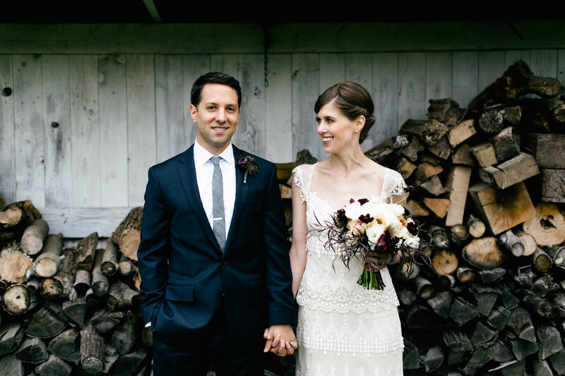 bride and groom in front of wood pile