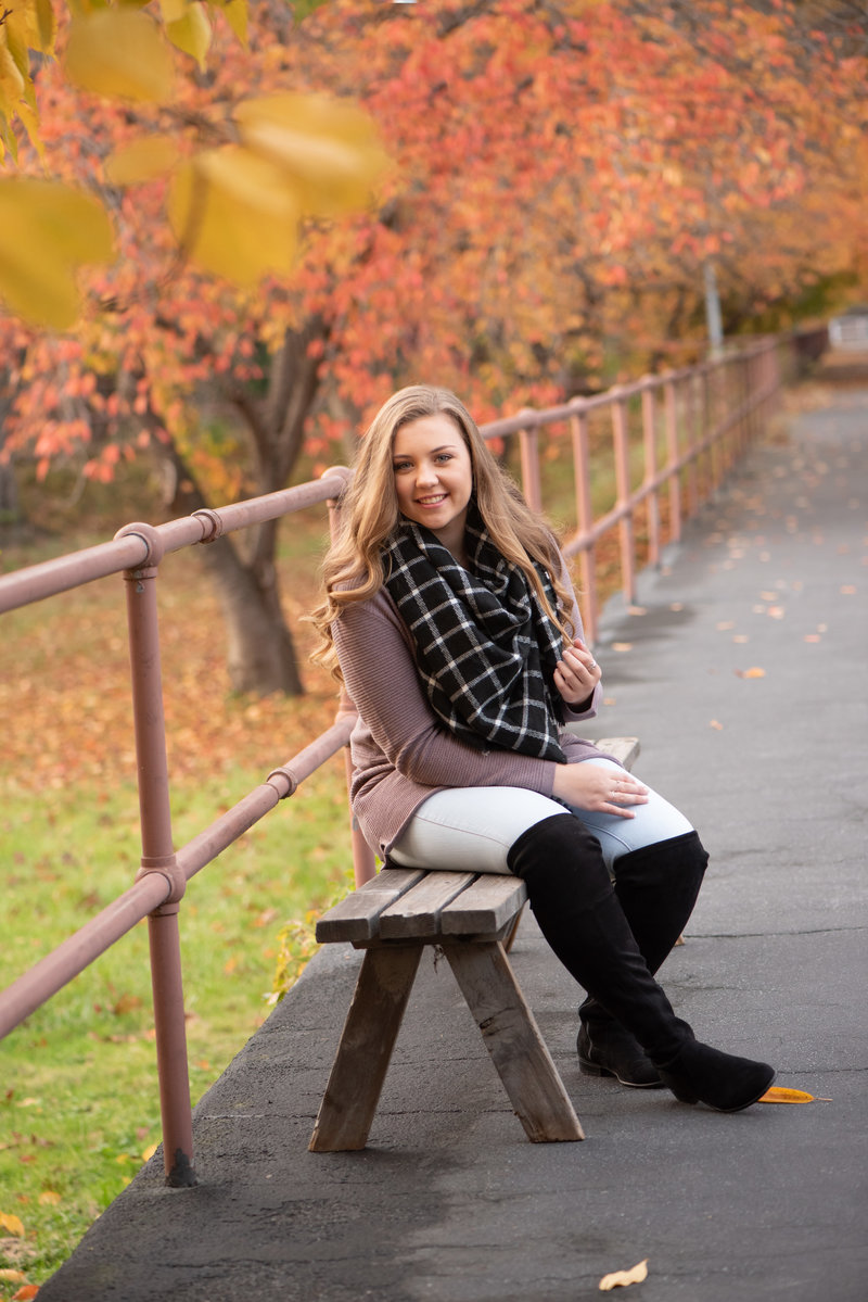 Senoir Girl Seated on bench along pathway lined with fall foliage