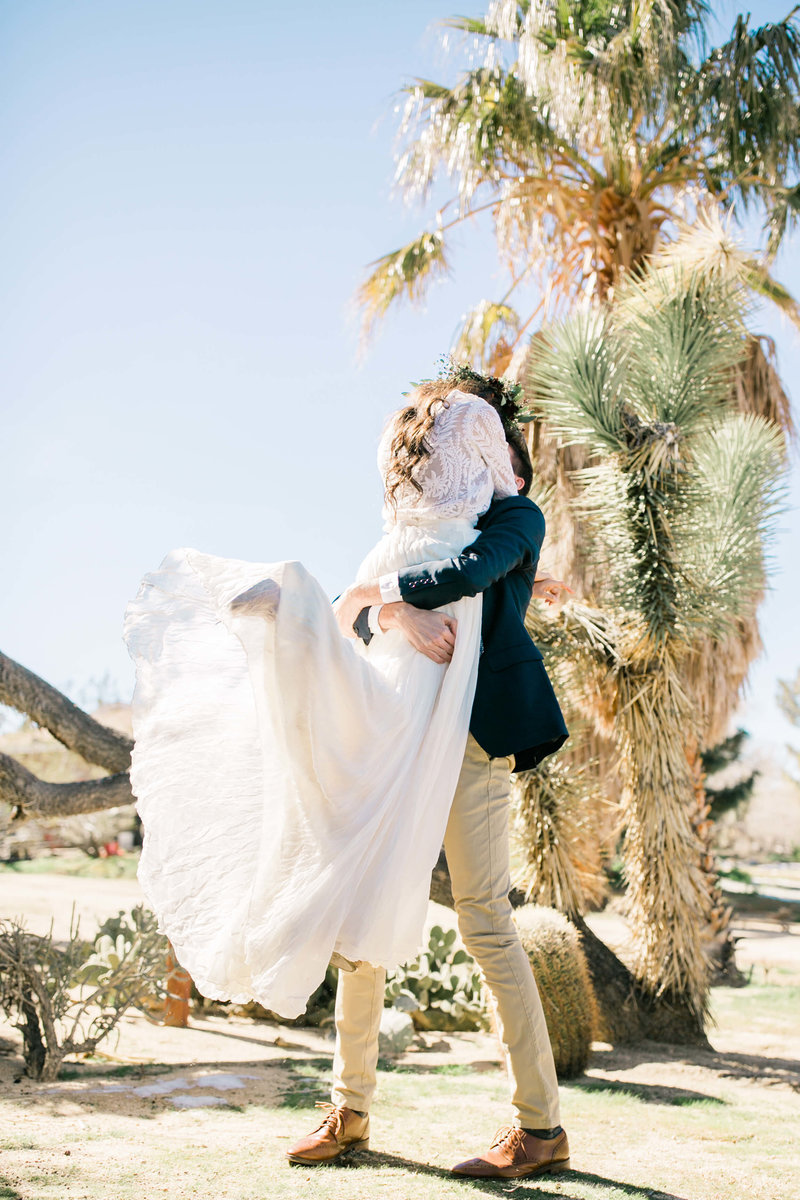 the groom lifts the bride off her feet during their elopement first look