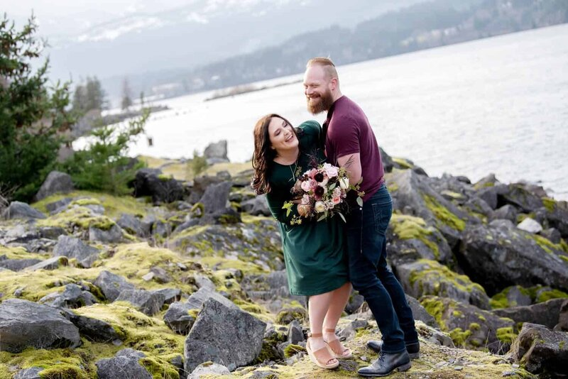 a man tickles a woman holding a pretty bouquet by flowers by alana overlooking the columbia river at Government Cove