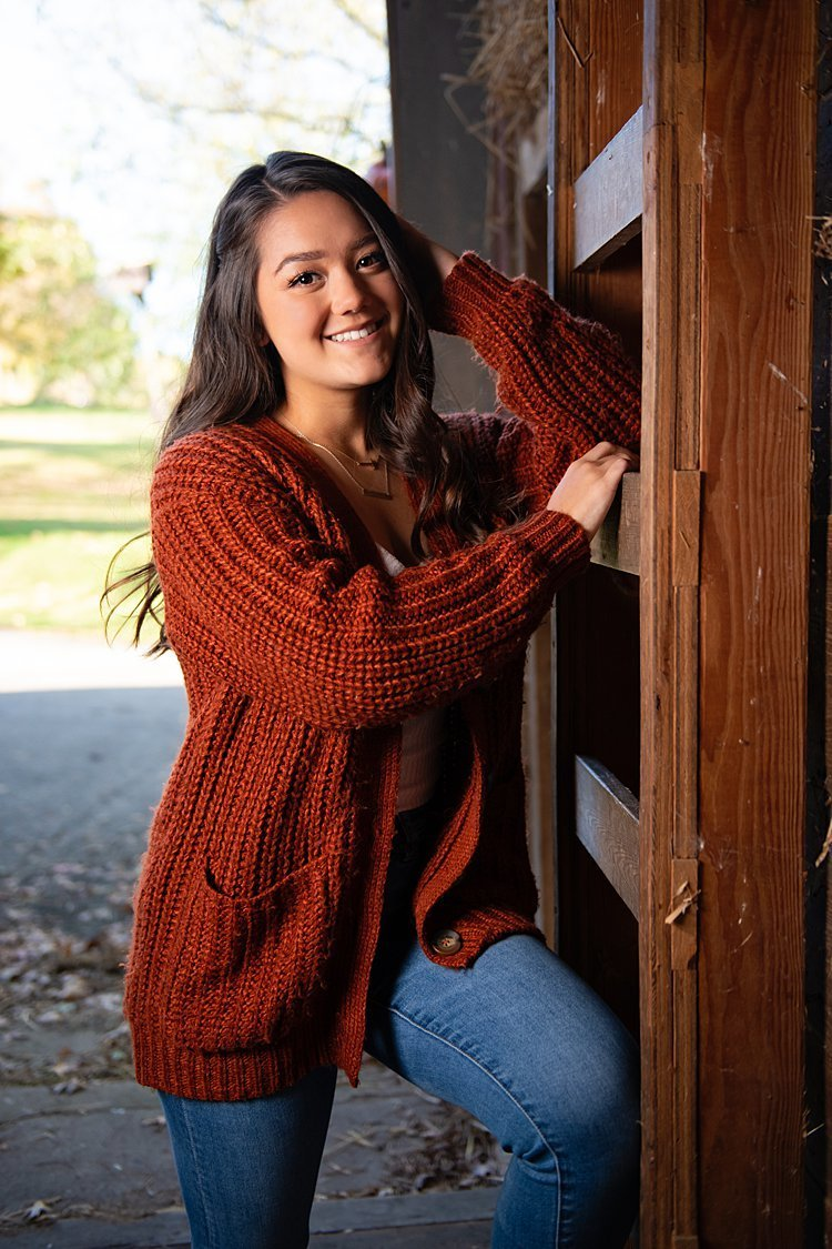 High school senior girl in rust-colored cardigan leaning on ladder in barn at Round Hill Park in Elizabeth, PA