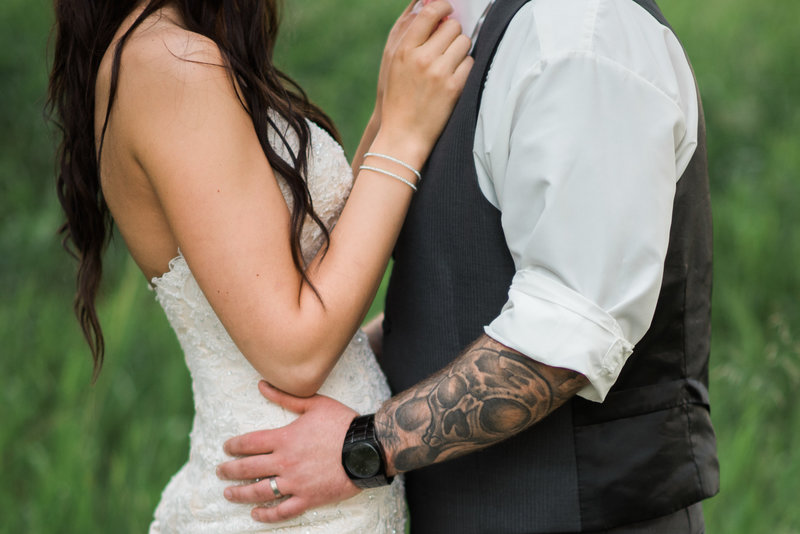 Red Deer Photographers-Raelene Schulmeister Photography- wedding photos-bride and groom photos in a field-spring wedding in Red Deer at the Valley Centre Hall-groom with tatoos