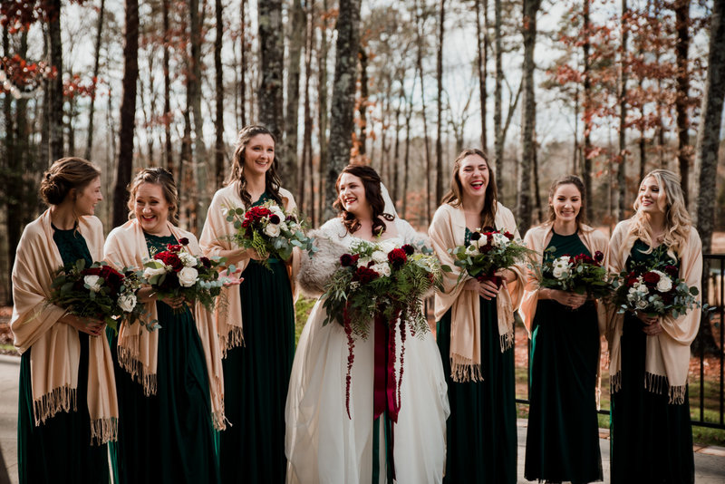 asheville elopement photographer, bride with bridesmaids laughing and looking at each other green dresses red flowers