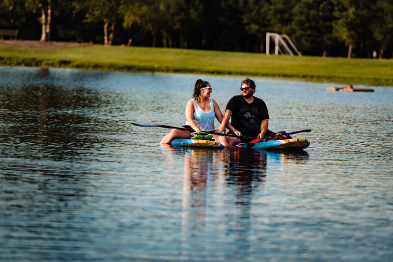 A man and a woman sit on paddle boards and laugh in the sunshine