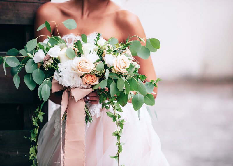 A bride in a blush wedding dress stands with a beautifully rustic bouquet tied with peach silk ribbon.
