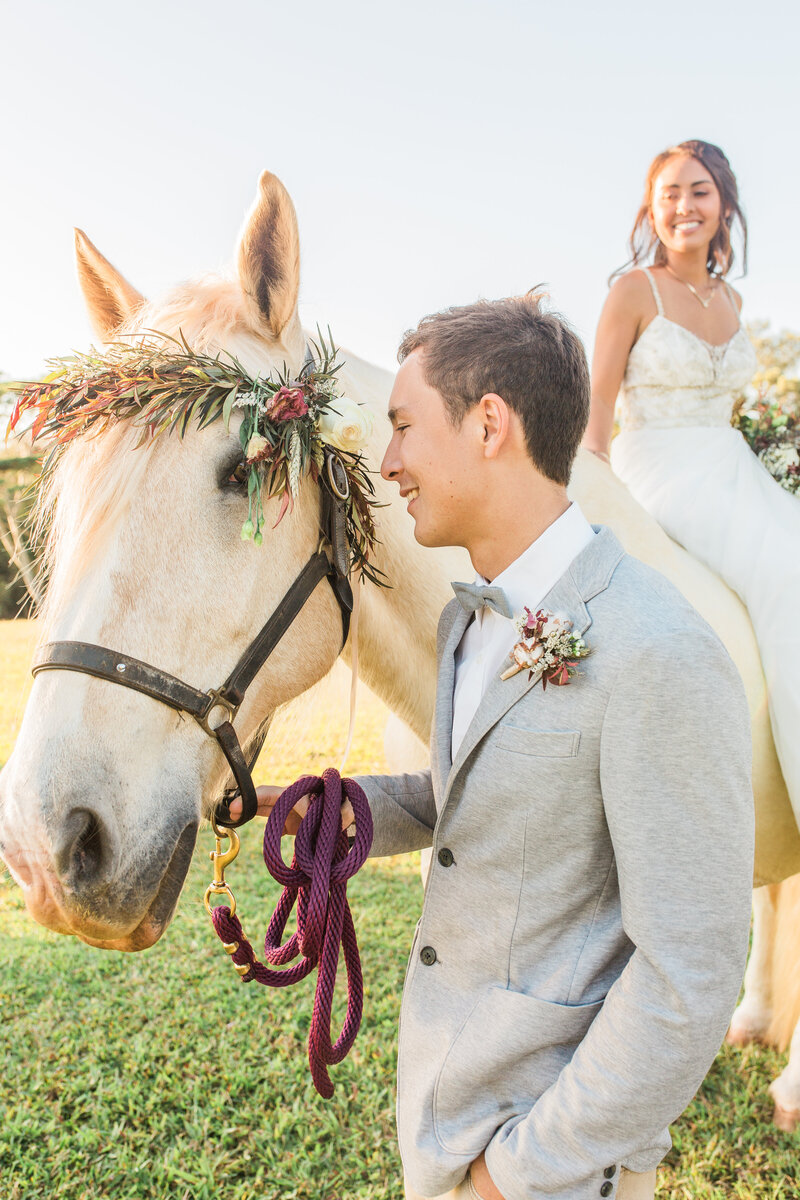 groom with white horse at sunset ranch hawaii