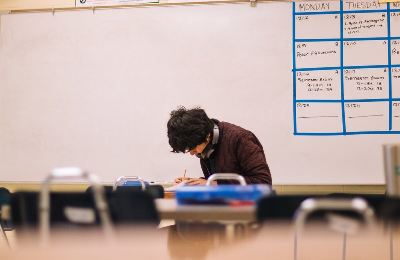 student sitting inside a classroom writing with a pencil