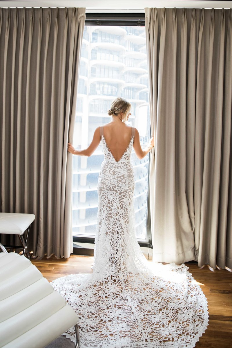 back of bride's dress looking out hotel room curtains