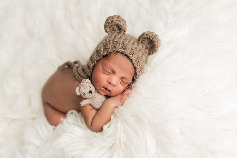 baby with stuffed bear and bear hat